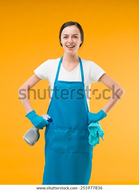 happy cleaning woman holding cleaning supplies and laughing, on yellow background