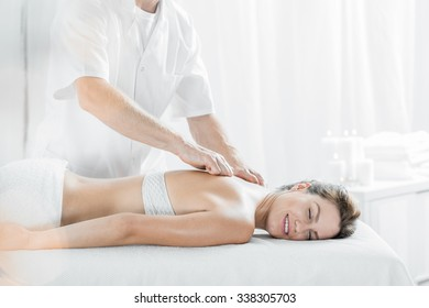 Happy client during relaxing massage in spa