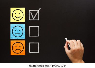 Happy client filling out a feedback survey with white chalk on blackboard. Customer satisfaction evaluation form concept.