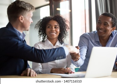 Happy clients african american couple handshake insurer broker bank manager make business deal take loan buy insurance, mixed race family customers realtor advisor shake hands sign mortgage contract