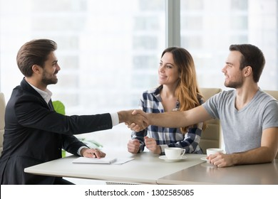 Happy clients couple handshake lawyer realtor financial adviser thanking for help, insurer salesman bank worker and millennial customers shake hands make mortgage loan deal, buy insurance services