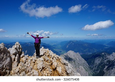 Happy climber on the ridge close to Zugspitze, Germany, with arms spread