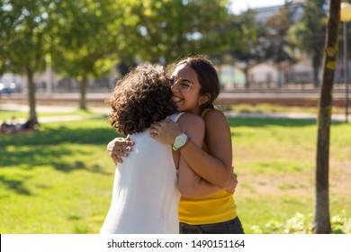 Happy close female friends greeting each other in park. Two women standing outdoors and hugging. Friendship concept