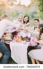 Happy close-up portrait of the delightful newlyweds and guests clinking their glasses and having fun at the setting table full of food and lovely flowers in the forest.