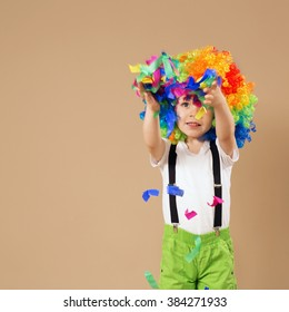 Happy clown boy with large colorful wig. Little boy in clown wig jumping and having fun. Portrait of a child throws up a multi-colored tinsel and confetti. Birthday boy.
