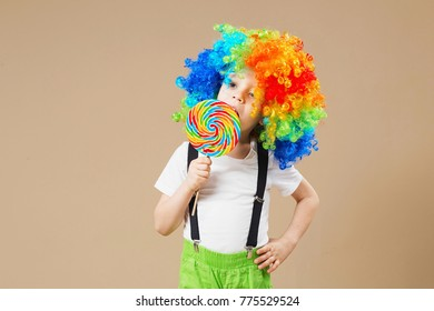 Happy clown boy in large colorful wig. Let's party! Funny kid clown. 1 April Fool's day concept. Portrait of a child eating lollipop. Birthday boy. Brazilian Carnival. Venice Carnival.