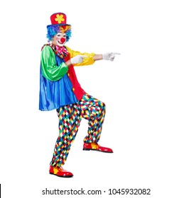 Happy clown in a hat imitating comic steps and pointing to the copy space area