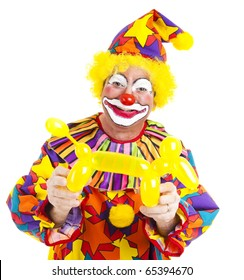 Happy clown holding a balloon dog he has made.  Isolated on white.