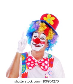 Happy clown pointing with hand to the copy space area