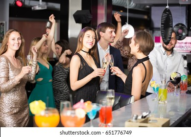 Happy colleagues dancing on corporate party with alcohol in hands