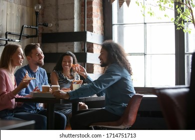 Happy  colleagues gather in pizzeria or bar have fun talking eating pizza, smiling  diverse friends hang out in cafe enjoying tasty Italian food, relaxing on weekend together