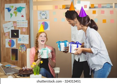 Happy colleagues giving birthday gifts to businesswoman in office