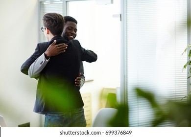 Happy colleagues greeting one another by embrace