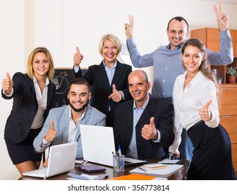 Happy colleagues looking at laptop and smiling