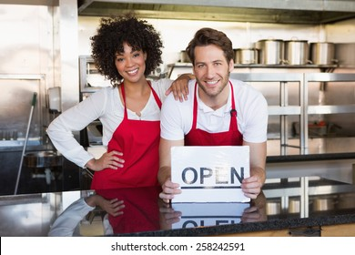 Happy colleagues posing with open sign at the bakery