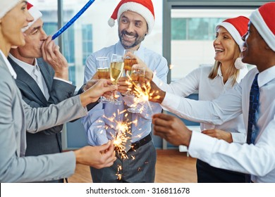 Happy colleagues in Santa caps having Christmas fun while toasting with champagne at party in office