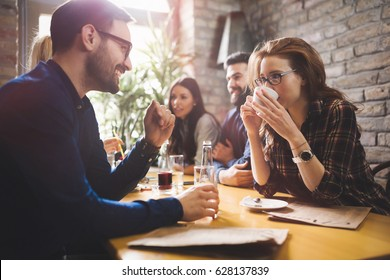 Happy colleagues from work socializing in restaurant and eating together