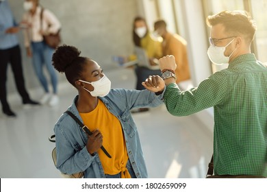 Happy college friends with protective face masks elbow bumping in a hallway.