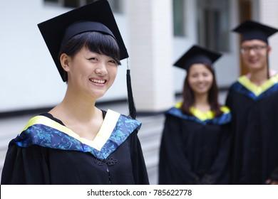happy college graduates smile at camera