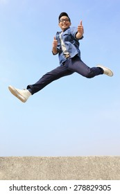 Happy College student man run and jump with blue sky background, full length, asian male