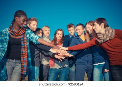 Happy College Students with Hands on Stack