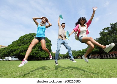 Happy College students jump and smile to you on campus lawn, asian