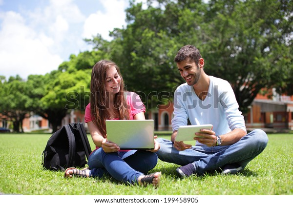 Happy College students using laptop and tablet pc on campus lawn, caucasian