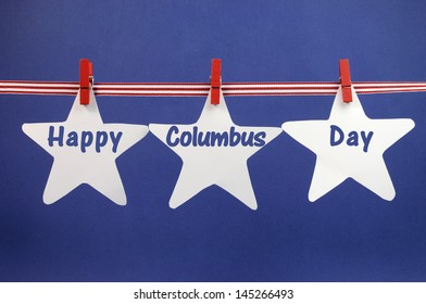 Happy Columbus Day message greeting written across white star cards hanging from red stripes ribbon and pegs on a line against a patriotic blue background for October 14.