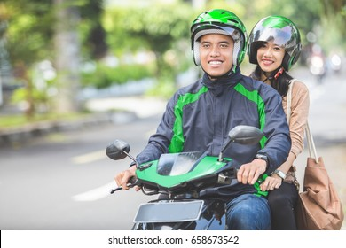Happy commercial motorcycle taxi driver taking his passenger to her destination