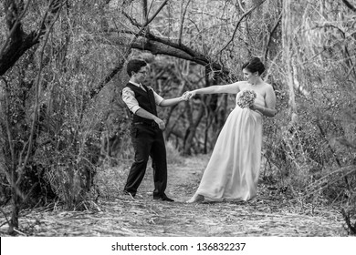 Happy committed couple dancing in the forest together