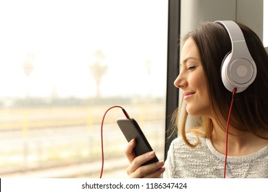 Happy commuter traveling into a train listening to music with a smart phone and headphones