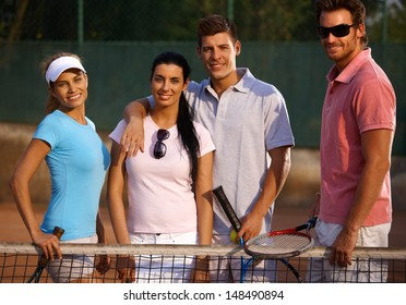 Happy companionship standing on tennis court, smiling.