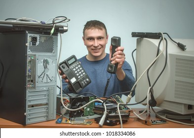Happy Computer technician engineer is showing in hand a phone. PC repair service center. Hardware repairman.
