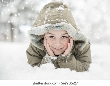 happy concept, enjoying the winter day, smiling boy lying in the snow
