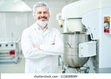 Happy confectionery factory employee standing in white coat with arms crossed and looking at camera.
