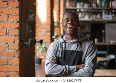 Happy confident african waiter small business owner portrait, positive black male entrepreneur looking at camera laughing standing in restaurant, cheerful businessman wear apron posing in coffeeshop