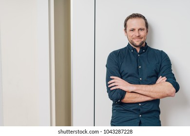 Happy confident attractive young man standing against a white internal wall with folded arms smiling at the camera