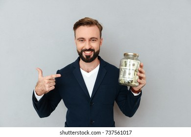 happy confident bearded man in official suit pointing at box with money isolated over grey