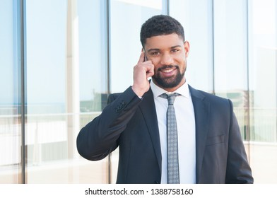 Happy confident businessman learning good news from phone talk. Young black man in formal suit speaking on cell and smiling at camera near office building. Business communication concept