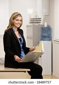 Happy, confident businesswoman sitting on desk holding notebook