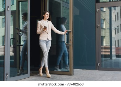 Happy confident businesswoman walking out of modern office center. Successful entrepreneur with smartphone outdoors.
