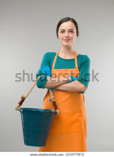 happy confident cleaning lady holding bucket with arms crossed, on grey background
