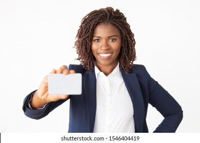 Happy confident female banker advertising credit card. Young African American business woman standing isolated over white background. Banking or payment concept
