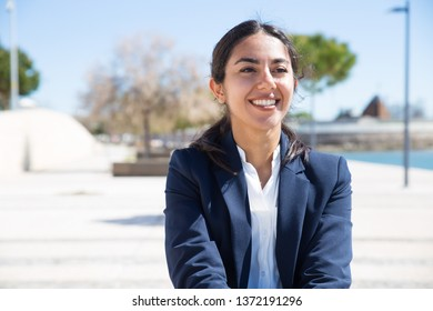 Happy confident professional enjoying walk on promenade during work break. Portrait of beautiful young business woman in formal jacket smiling and looking away. Outdoor business portrait concept