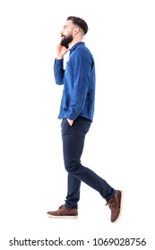 Happy confident successful business man walking and talking on cell phone with hands in pockets looking up. Full body isolated on white background.