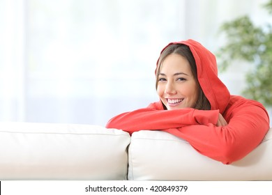 Happy confident teen girl in red posing and looking at camera at home