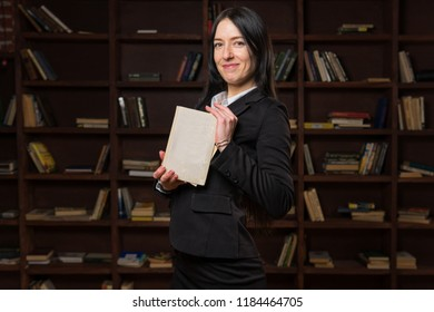 Happy confident woman holding book near bookshelf in library