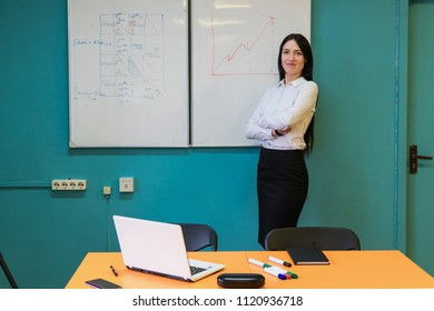 Happy confident woman teacher standing with crossed arms near whiteboard in university classroom