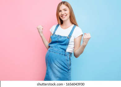 A happy confident young beautiful pregnant woman in a denim jumpsuit shows a winning gesture while standing on an isolated pink and blue background