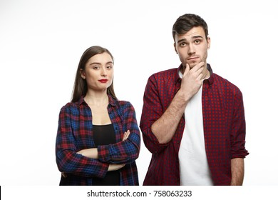 Happy confident young brunette woman smiling standing in studio with arms folded next to her uncertain boyfriend who is touching his chin, feeling doubtful and hesitant about buying new car